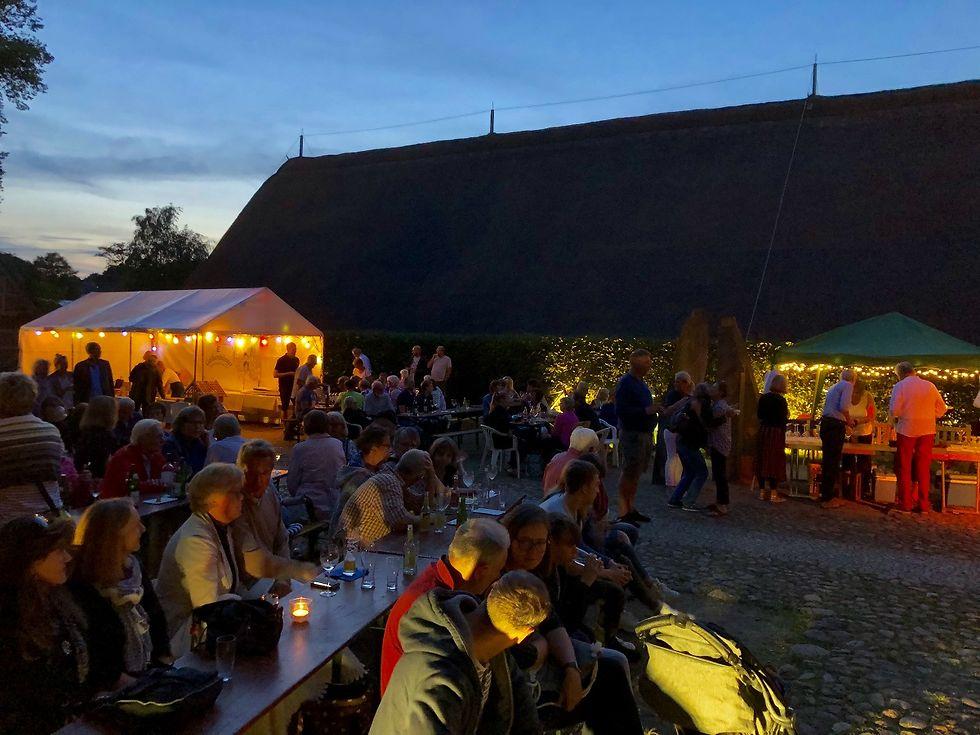 Besucher*innen genießen die Atmosphäre beim Kleinen Schlossfest im Ehrenhof.
