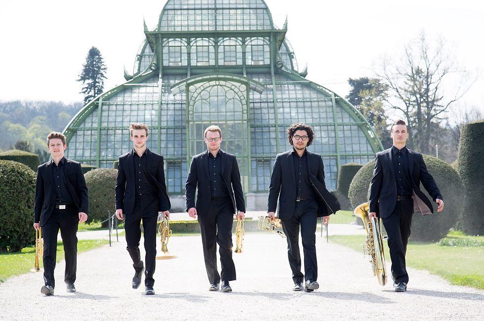 Fünf junge Musiker in Konzertkleidung und mit ihren Instrumenten vor einem Gewächshaus.