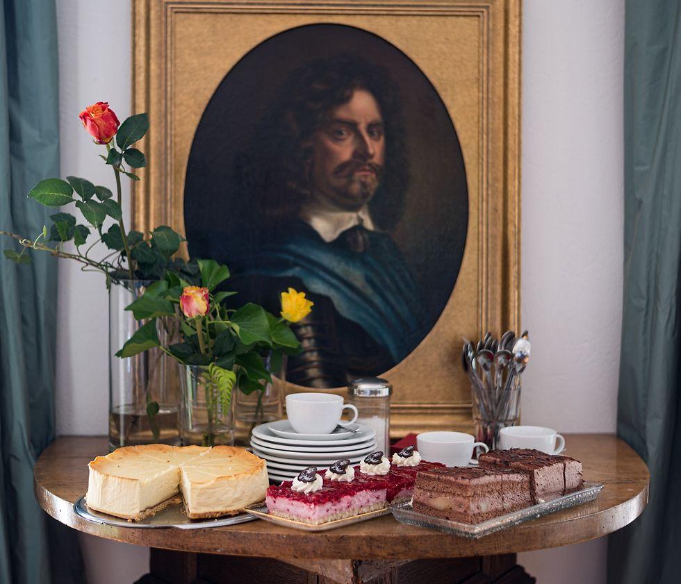 Kuchen, Geschirr und Blumen vor einem Porträt in einem Goldrahmen.