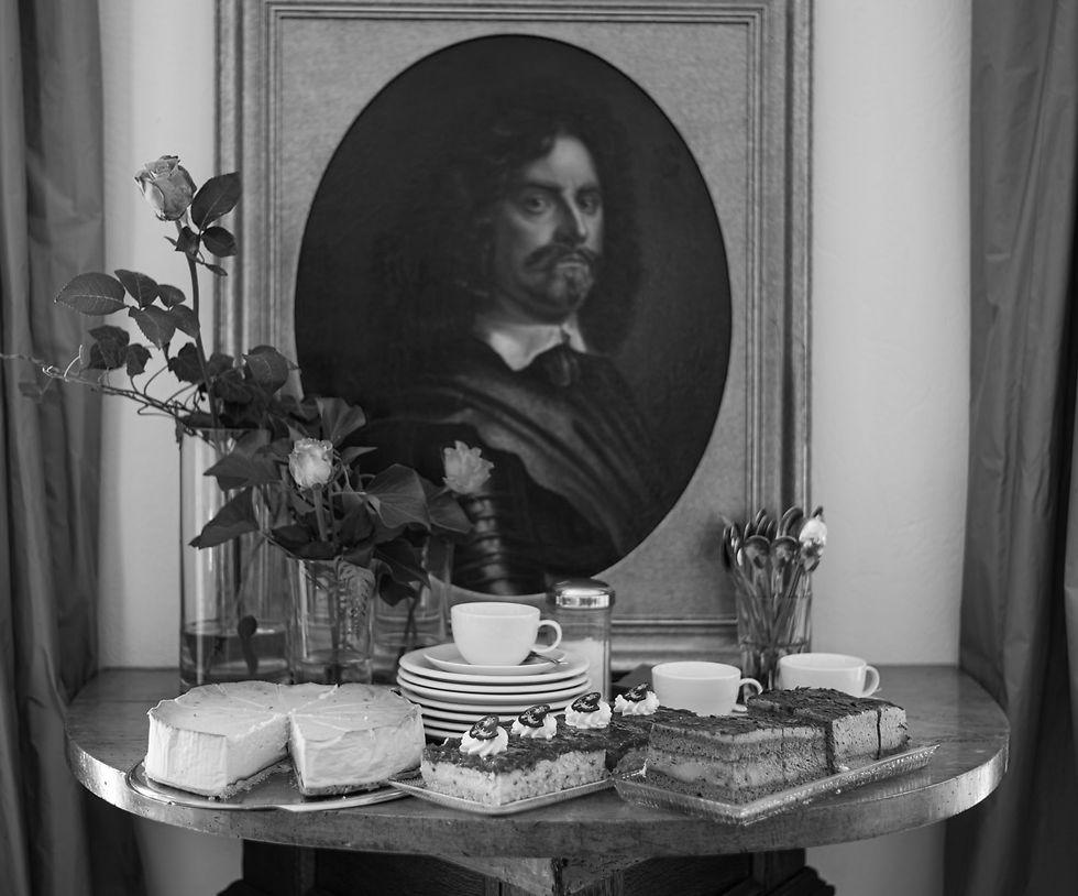 Kuchen, Torten, Geschirr und Blumenschmuck sind vor dem Porträt des Schlosserbauers angerichtet.