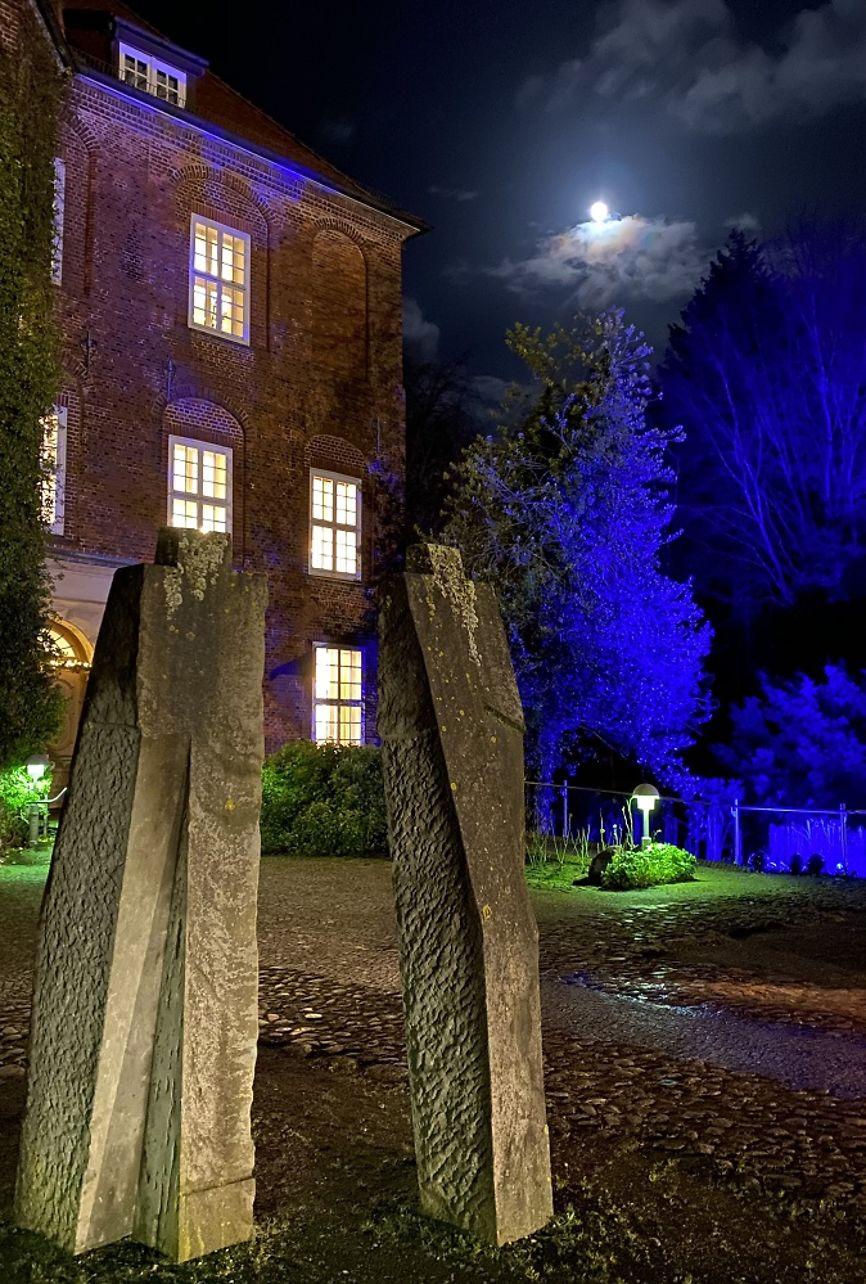 Zwei große, grob menschlich aussehende Steinskulpturen. Dahinter sieht man die Schlossfront mit erleuchteten Fenstern und blau angestrahlten Bäumen.
