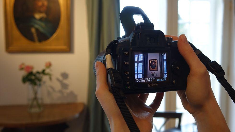 Hände halten eine Kamera. Auf dem Display und im Hintergrund sieht man ein Gemälde.