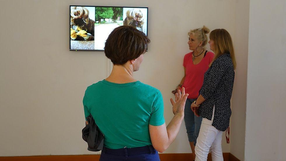 In einem Ausstellungsraum betrachten drei Frauen einen Bildschirm.