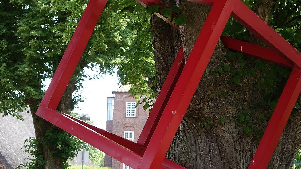 Ein roter Metallwürfel hängt an einem Baum.