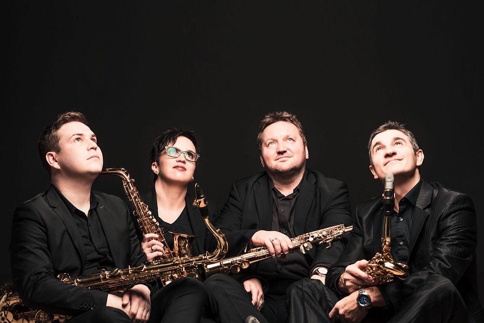 Das Quartett in schwarzer Konzertkleidung vor schwarzem Hintergrund mit ihren Saxophonen.