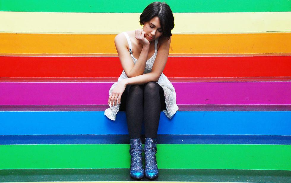 Die Sängerin sitzt auf regenbogenfarbenen Stufen.