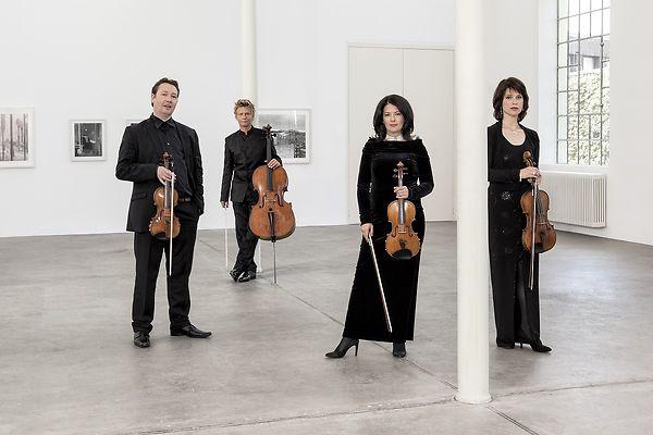 Vier Musiker in schwarzer Konzertkleidung stehen in einem großen weißen Raum verteilt.