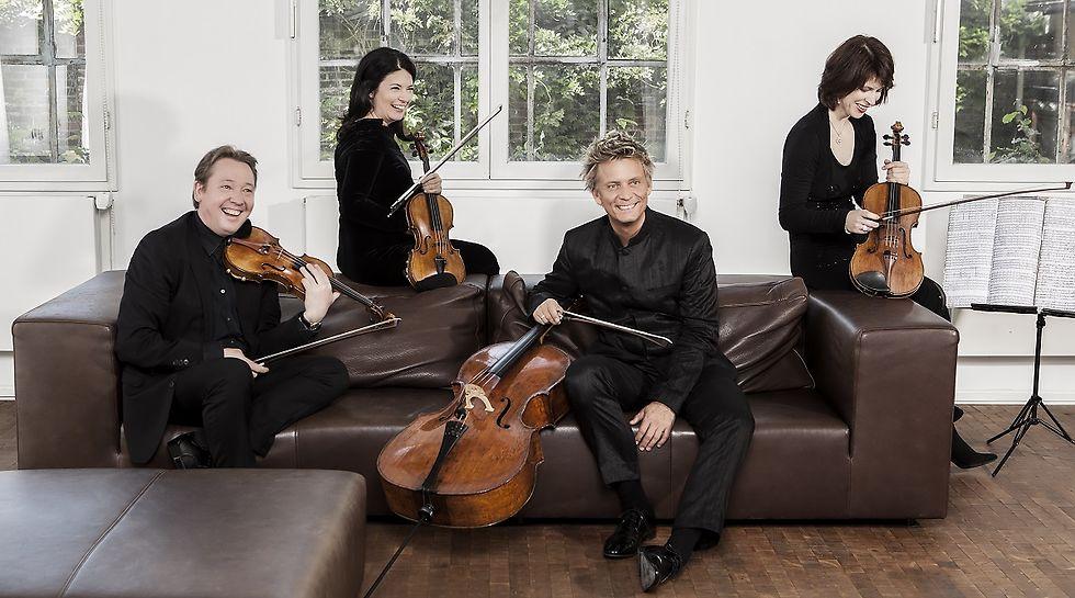 Vier Musiker*innen in schwarzer Konzertkleidung und ihren Instrumenten auf einem braunen Ledersofa.
