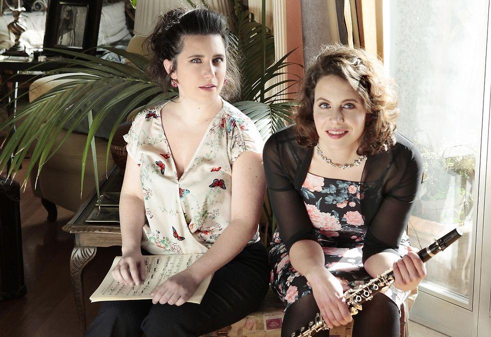 Die zwei Musikerinnen sitzen nebeneinander in einem Wohnzimmer. Eine hält Notenblätter, die andere eine Klarinette in der Hand.