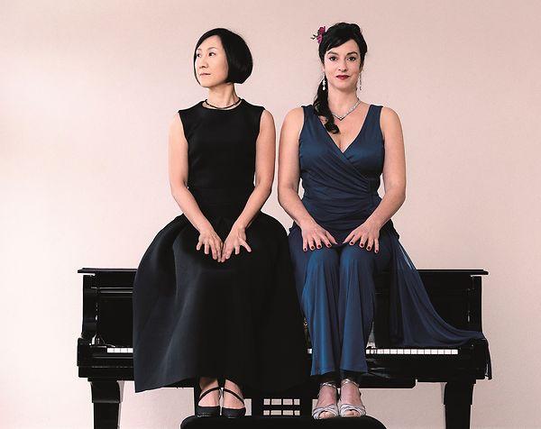 Jeong-Min Kim und Franziska Dannheim sitzen in Abendkleidern auf dem Flügel.