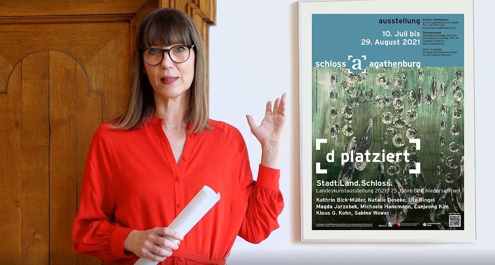 Claudia Rastzar zeigt auf das Plakat zur Ausstellung.
