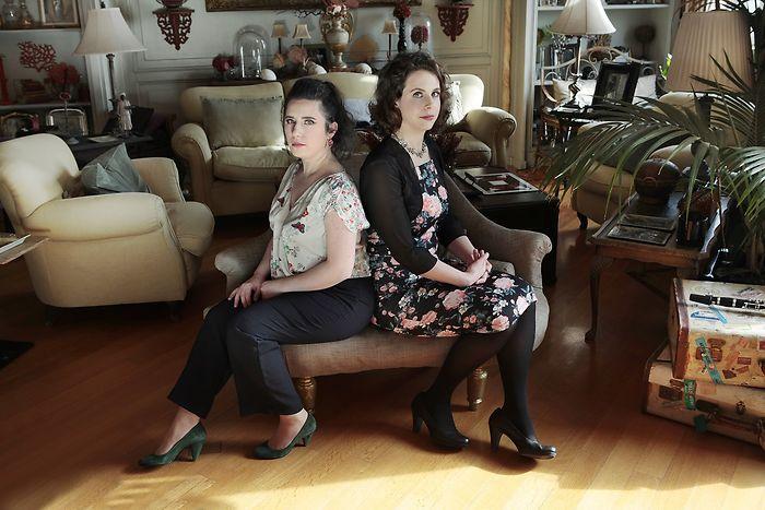 Die zwei Musikerinnen sitzen Rücken an Rücken in einem Wohnzimmer.
