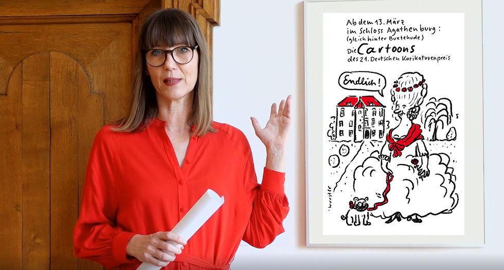 Claudia Rasztar deutet auf eine gerahmte Karikatur.