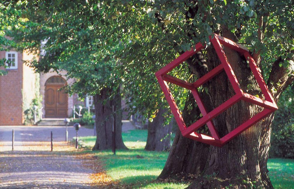 Ein roter Kubus aus Metall hängt in einem Baum vor dem Schloss.
