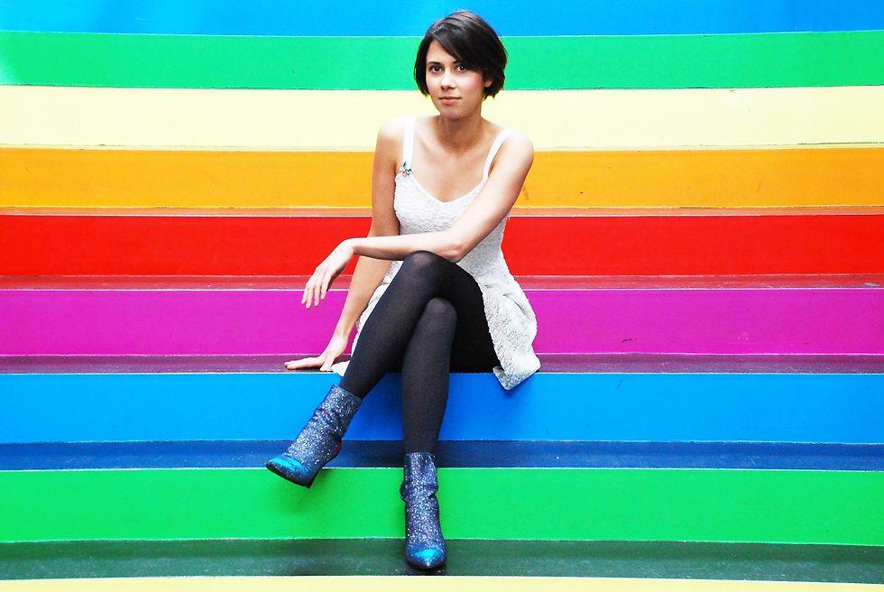 Die Sängerin sitzt auf Stufen in den Farben des Regenbogens.