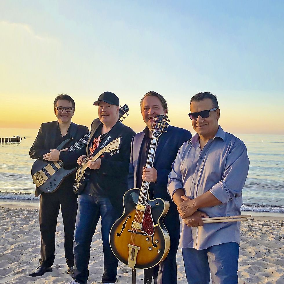 Gruppenbild der vier Musiker am Strand.