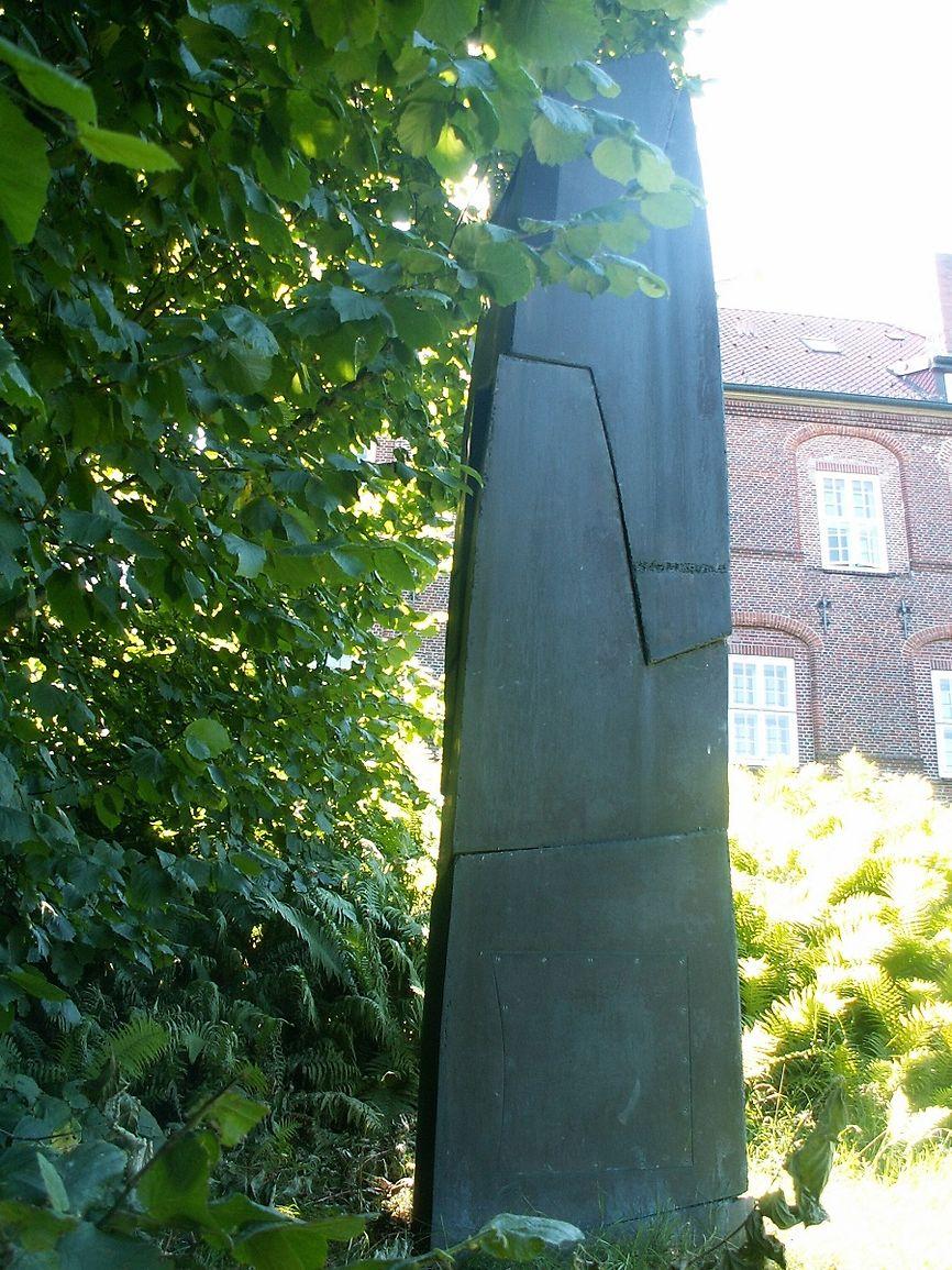 Eine Stele aus Bronze, im Hintergrund sieht man das Schloss.