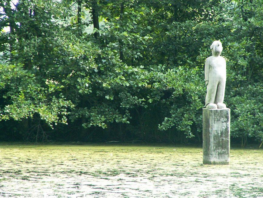 Eine aus Holz geschnitzte Figur eines Männchens steht auf einem Pfahl mitten im Teich.