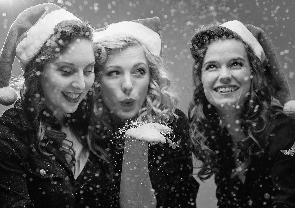 Die drei Sängerinnen mit roten Weihnachtsmützen in einem künstlichen Schneegestöber.