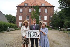 Rosemarie Meyer, Henning Porth und Bettina Roggmann halten gemeinsam einen übergroßen Scheck. Im Hintergrund sieht man das Schloss.