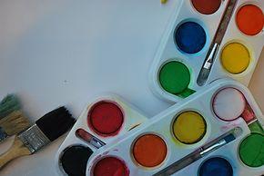 Drei Paletten Wasserfarben und Pinsel.
